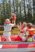Grandparents and grandchildren enjoying boat trip on lake Stock Photos