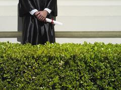 Yliopisto-opiskelija valmistumisen puku tilalla tutkintotodistus, mid-osio, hedge Kuvituskuvat