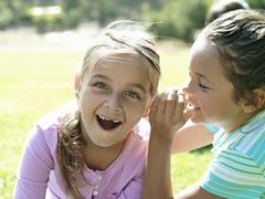Girl (7-9) whispering in friend's ear, second girl gasping, close-up Stock Photos