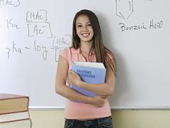 Teenage girl (15-17) standing beside whiteboard in classroom, holding textboo Stock Photos