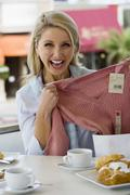 Woman sitting at cafe table, holding new top with price tag attached, smiling Stock Photos