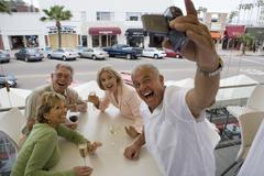 two senior couples sitting at restaurant balcony table, man filming with camc - stock photo