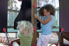 Two girls (3-5) playing in adventure playground, smiling Stock Photos