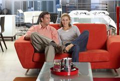 couple sitting on new red sofa in furniture store, man glancing at woman, smi - stock photo