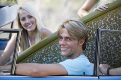 Teenage couple (17-19) sitting in car with surfboard, smiling, side view, por Kuvituskuvat