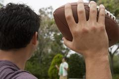 two teenage boys (17-19) playing american football in park, focus on foregrou - stock photo
