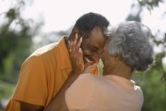 Affectionate senior couple embracing in park, face to face, smiling, close-up Stock Photos