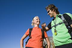 couple with rucksacks standing in valley, man leaning on woman's shoulder, sm - stock photo