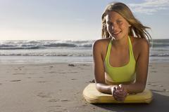 teenage girl (17-19) lying on top of bodyboard on sandy beach, smiling, front - stock photo