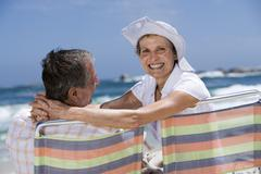 Affectionate senior couple sitting in beach chairs, smiling, rear view, portr Stock Photos