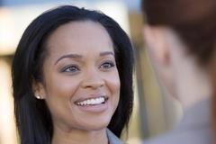 businesswoman talking to colleague, smiling, close-up (differential focus) - stock photo