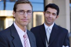 Two businessmen standing outside building, smiling, portrait (differential fo Stock Photos