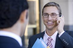 Businessman in spectacles using mobile phone, smiling, close-up (differential Stock Photos