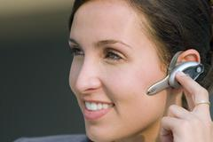 businesswoman wearing mobile phone hands-free device, smiling, close-up - stock photo