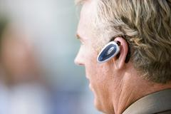 Mature businessman wearing mobile phone hands-free device, close-up, profile Stock Photos