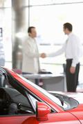 Salesman shaking hands with male customer in car showroom, focus on red conve Stock Photos
