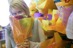 Woman smelling flower bouquet beside shop display in florists, face obscured, Stock Photos
