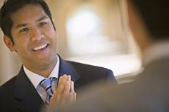 Respectful businessman greeting counterpart in building arcade, smiling (diff Stock Photos