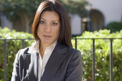 Businesswoman, in grey suit, standing beside communal garden railing, close-u Stock Photos