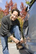 Man leaning against car bumper, tying shoelace, smiling, portrait Stock Photos