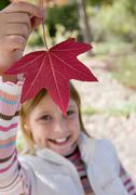Girl (7-9) holding aloft red maple leaf in park in autumn, smiling, close-up, Stock Photos