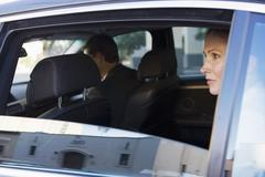 Businesswoman sitting in back-seat of chauffeur driven car, looking out of op Stock Photos