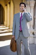businessman standing in colonnade, carrying briefcase, using mobile phone, la - stock photo