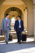 Two businessmen walking side by side in building arcade, luggage in tow, talk Stock Photos