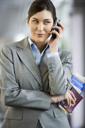 businesswoman standing in airport terminal, holding ticket, using mobile phon - stock photo