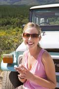 young woman standing in front of parked jeep on dirt track, using mobile phon - stock photo