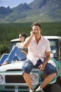 Young couple sitting on bonnet of parked jeep in mountain valley, man using m Stock Photos