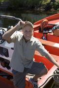 Senior man standing in motorboat beside lake jetty, tilting cap, smiling, por Stock Photos