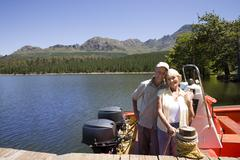 Senior couple standing in motorboat beside lake jetty, woman tying rope to mo Stock Photos