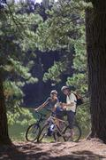 young couple, with rucksacks, mountain biking along woodland trail beside lak - stock photo