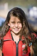 Girl (7-9) wearing red life jacket, smiling, close-up, front view, portrait Stock Photos