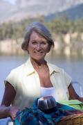 Senior woman carrying picnic hamper beside lake, smiling, portrait Stock Photos