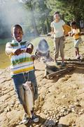 family cooking food on camping trip beside lake, boy (8-10) holding aloft fis - stock photo