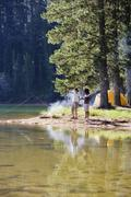 Couple, in mid-distance, fishing near lakeside campfire, woman holding aloft  Stock Photos