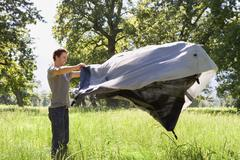 Man assembling tent on camping trip in woodland clearing, side view Stock Photos