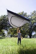 Young man standing in woodland clearing, lifting lightweight grey dome tent i Stock Photos