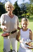 Grandmother and granddaughter (8-10) serving barbecued food in garden, girl h Stock Photos