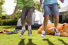 Brother and sister (8-10) jumping in front of incomplete dome tent on garden  Stock Photos