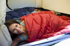 Family camping in tent, children (8-10) sleeping in background, focus on moth Stock Photos