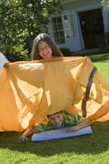 Brother and sister (8-10) assembling tent on garden lawn, girl sitting on top Stock Photos