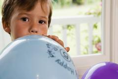 Boy (4-6) sitting on window seat at home, blowing air into blue party balloon Stock Photos