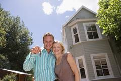 Couple standing in driveway in front of detached house, man holding aloft set Stock Photos