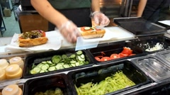 Stock Video Footage of Sandwiches preparation in local fast food store.