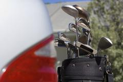 Set of golf clubs beside parked car on driveway, close-up (differential focus Stock Photos
