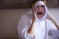 Cheerful woman wrapping piece of paper around face, mouth open, portrait Stock Photos