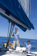 Father and son (8-10) standing at helm of sailing boat out to sea, boy steeri Stock Photos